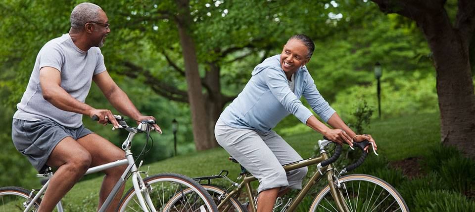 An African American couple bikes in a park.