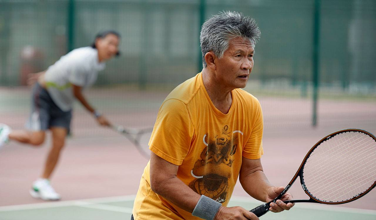 A asian man stands holding a tennis racket, while his partner completes a serve in the background.