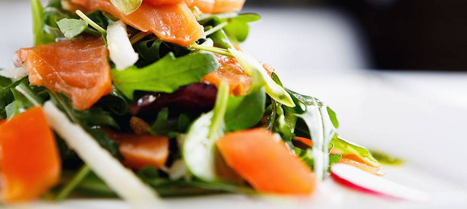 A leafy salad topped with fresh salmon