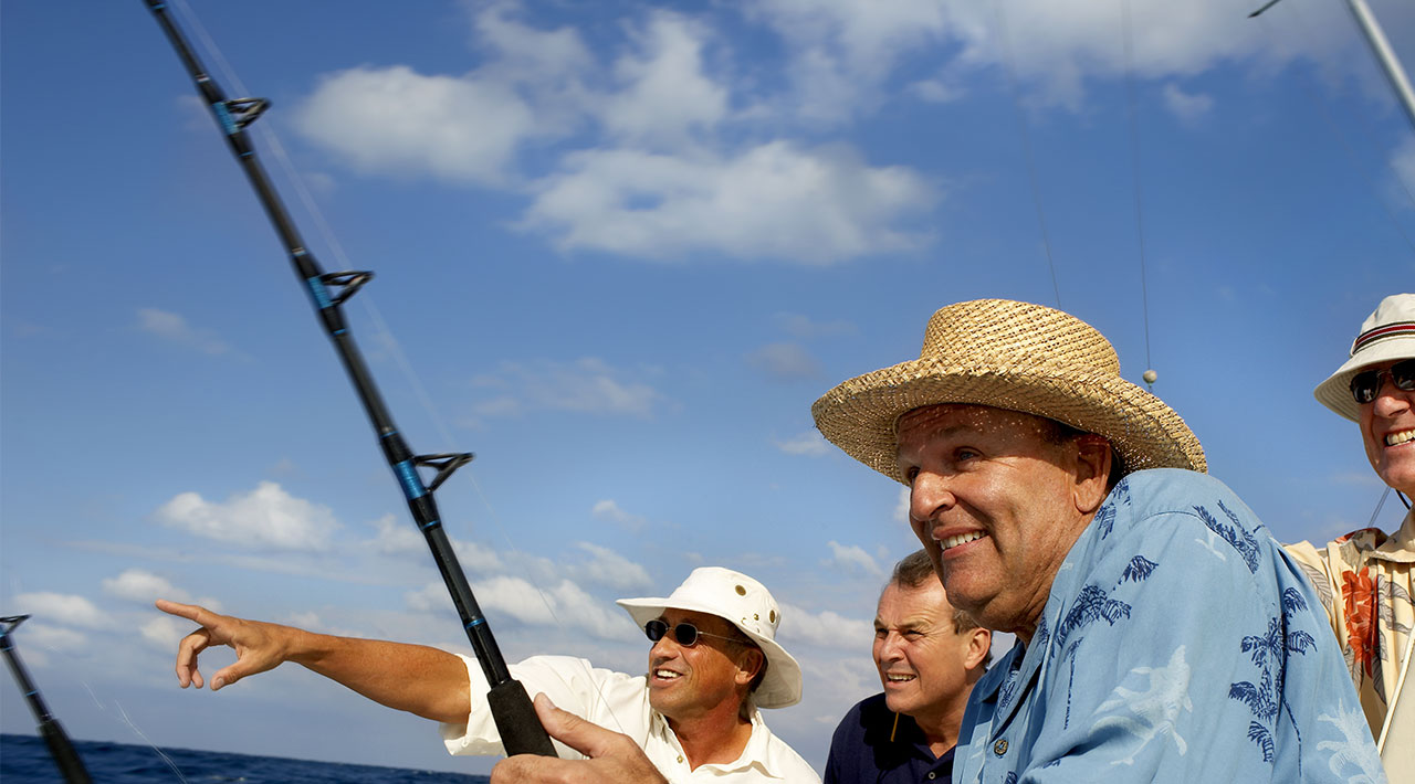 Active senior men on a fishing boat; men are wearing summer hats and bright shirts.