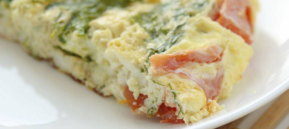 Close up  of an omelet with spinach and tomato.