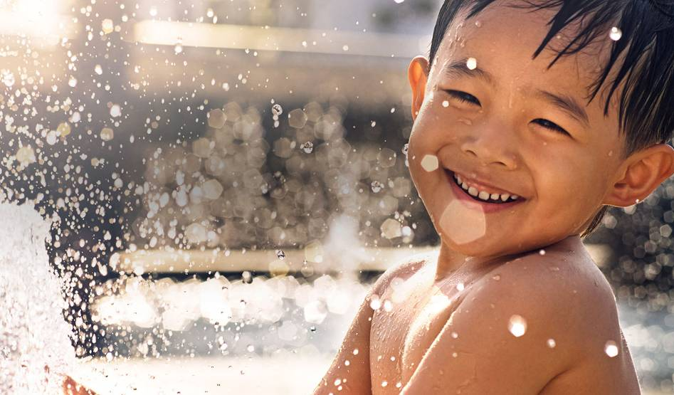 An young boy playing in a fountain and laughing.