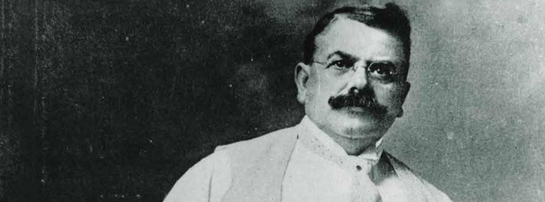 Fotografía en blanco y negro de Wallace C. Abbott.  Tiene el pelo oscuro y corto y un gran bigote oscuro y lleva gafas y una camisa blanca, un traje con chaleco y corbata.