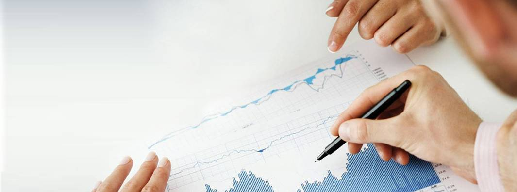 Close-up of the hands of two women pointing at a graph and one man's hand holding a pen ready to markup the report.