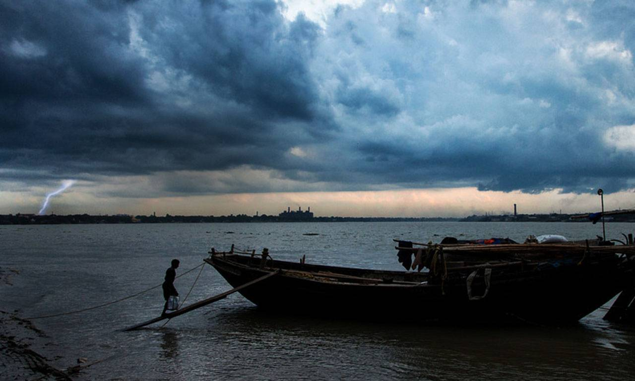 Dark clouds over water; Lightening in the distance with a fisherman and boat in the foreground.