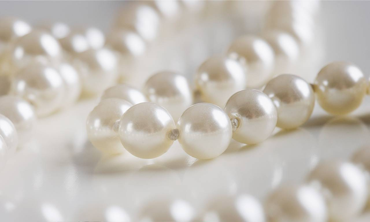 A close-up of a strand of white pearls.