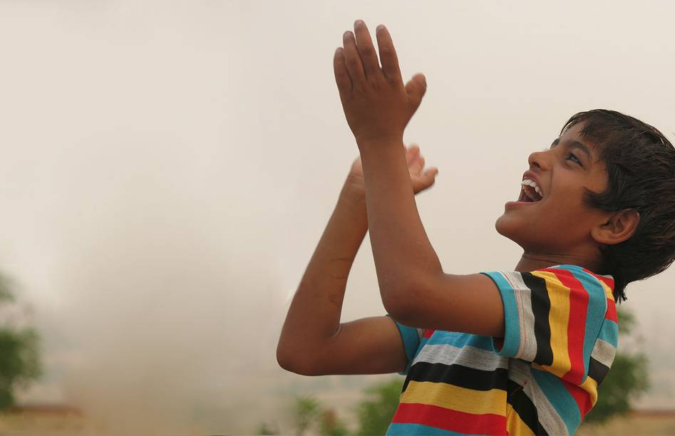 Young Indian boy in multi-colored striped t-shirt,laughing and clapping his hands as he looks at something he sees in the sky.