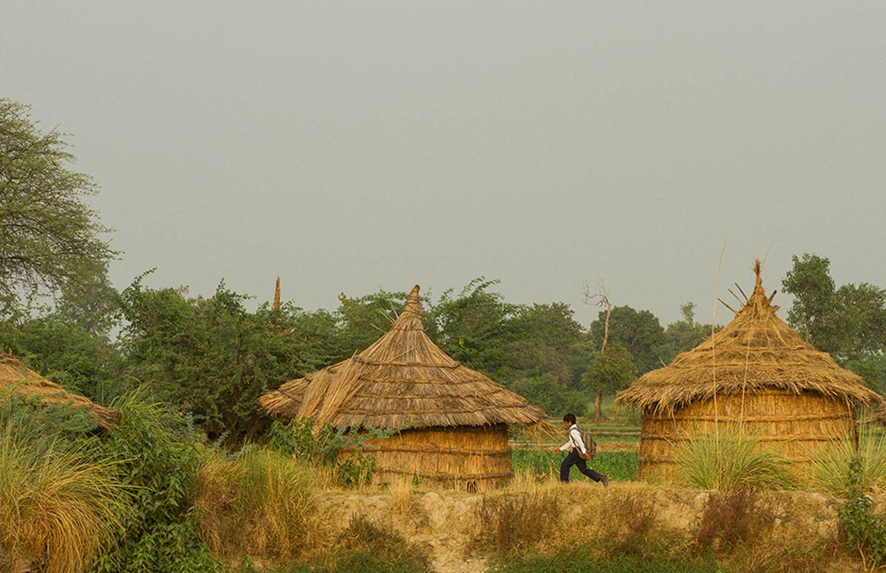 Young asian boy in school uniform, wearing a heavy backpack, walking past two straw huts nestled amoungst lush trees and bushes.