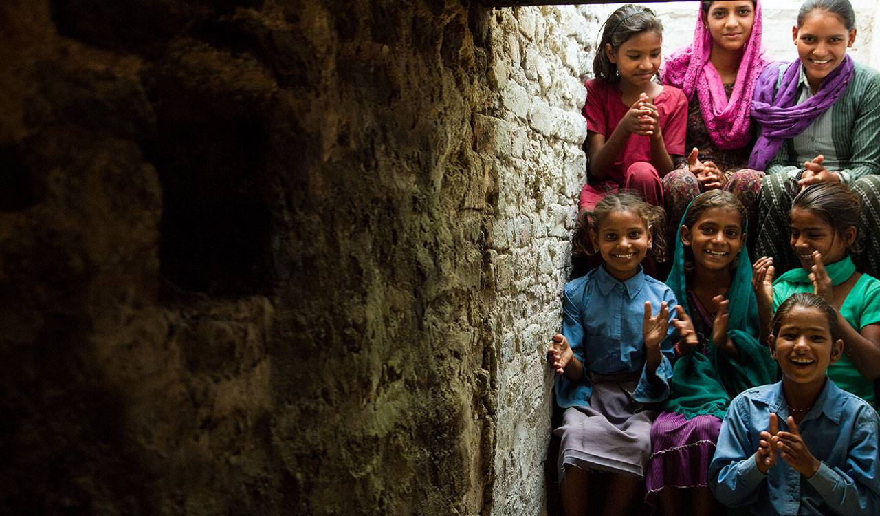 A group of young, Indian girls are smiling and clapping as they sit together on a stone staircase.