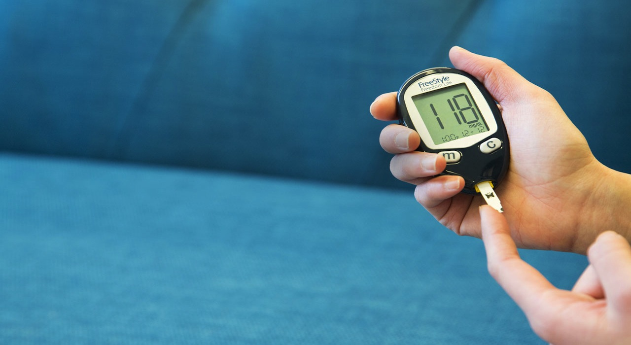 Testing glucose with FreeStyle Freedom Lite monitor; close-up of hands.