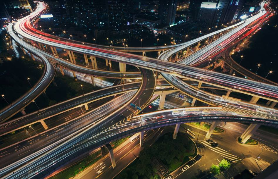 An aerial view of busy highway interchange at night.  Blurred headlights and tail lights extend into the distance.