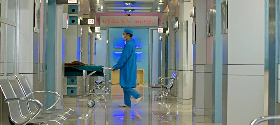 A hospital orderly in blue walks past the empty waiting room of a modern hospital.