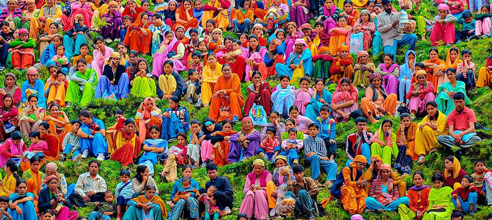 A crowd of people sitting on a hill wearing brightly colored clothes