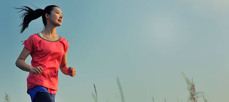 An Asian woman with long hair and a pink shirt jogs through a meadow against a clear blue sky.