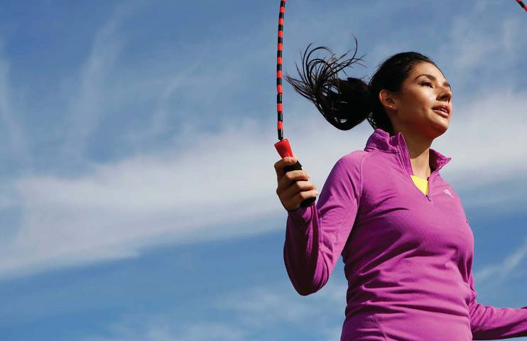 A woman in a ponytail and a bright pink athletic shirt jumps rope.