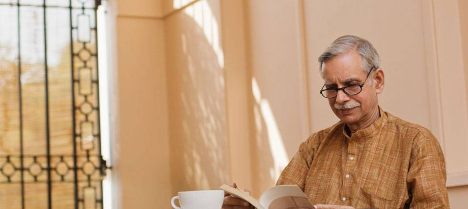 An elderly man wearing glasses and a moustache reads a book during his morning tea.