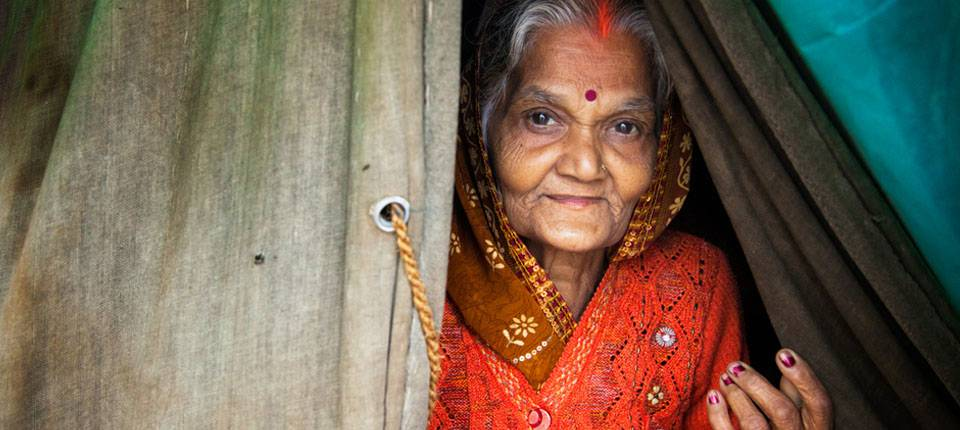 A smiling woman in a sari looks out of curtains in a doorway.