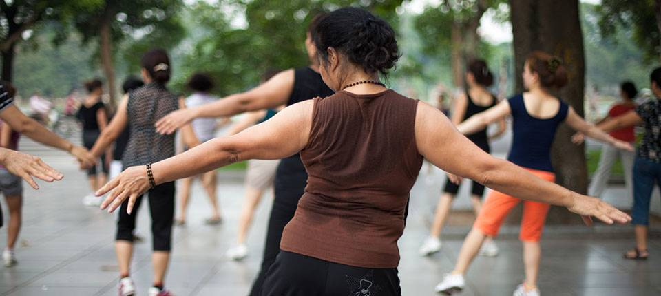 A group of women performing Tai-Chi in a large public space.