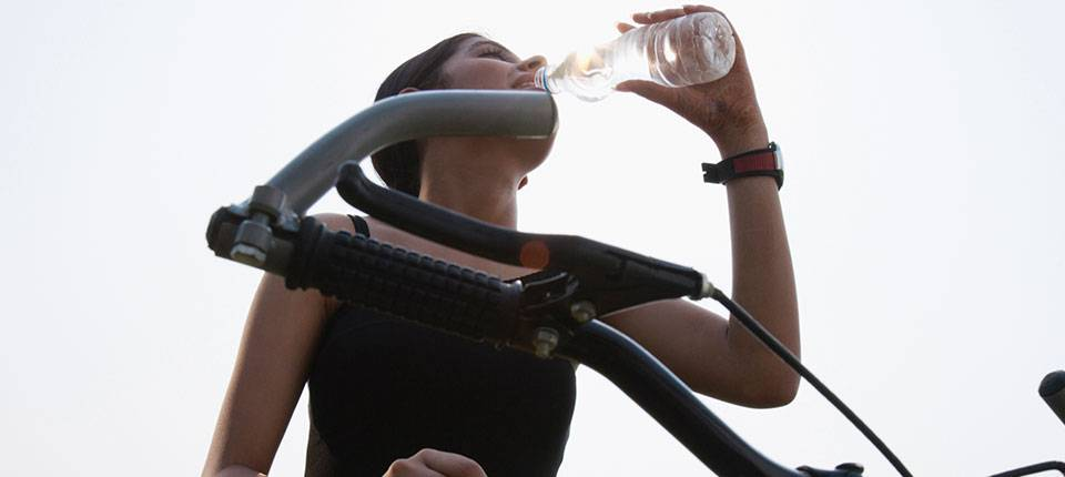 Woman on a mountain bike stops to drink water from a bottle.