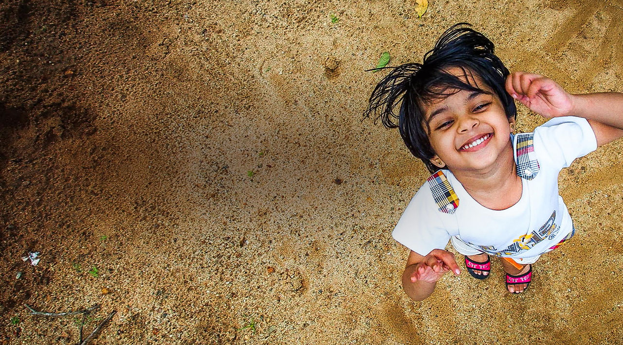 A young Indian girl stands on sandy ground and looks up with a big smile.