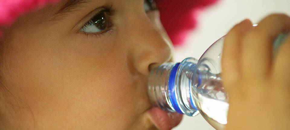 A toddler in a pink hat drinking bottled water.