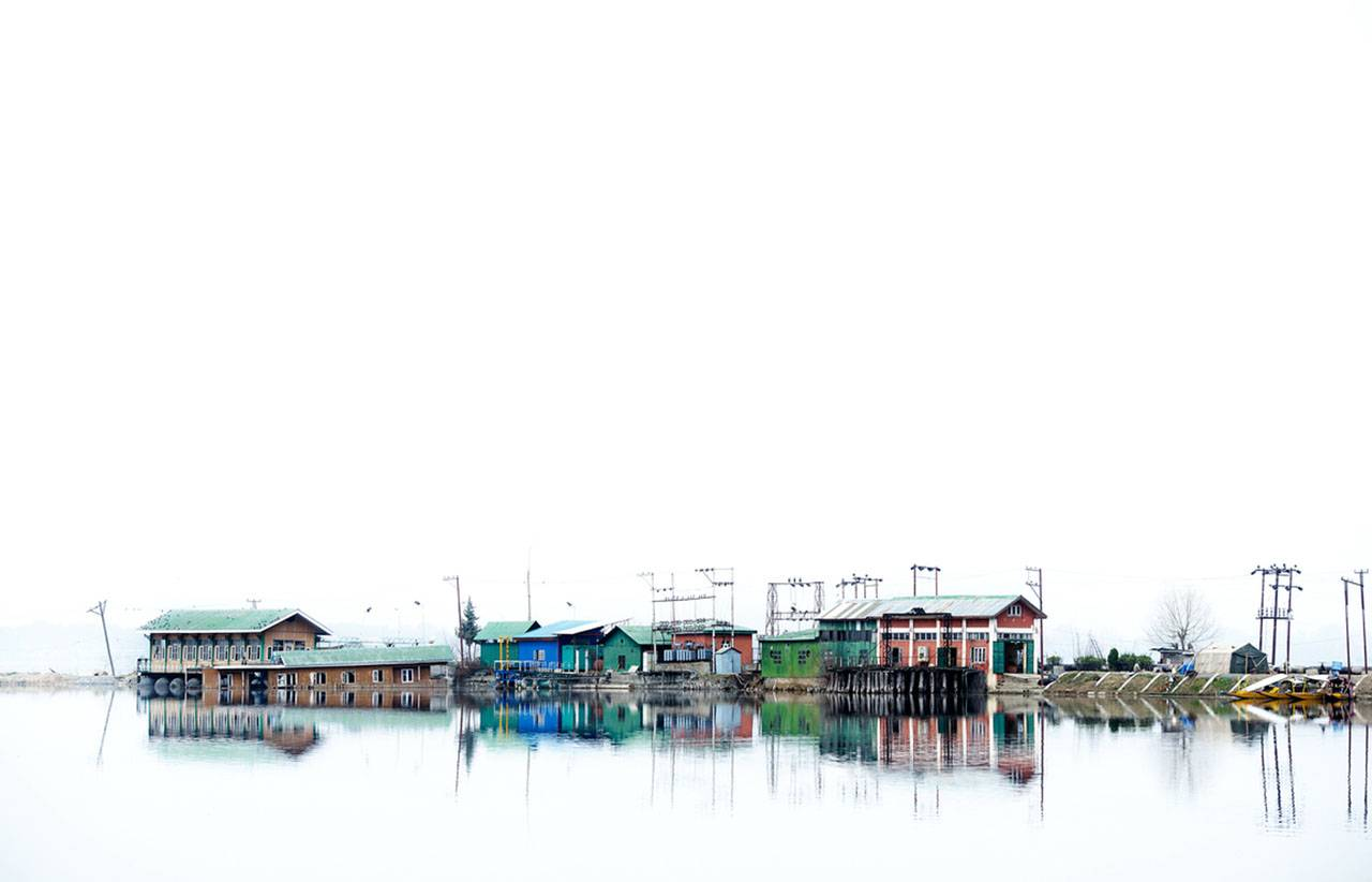 A tight grouping of colorful fishermen's cabins sit on stilts in a lake; the cabins are reflected in the water.