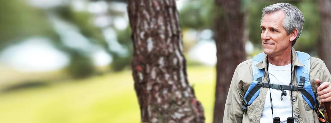 バックパックと双眼鏡を持って森でハイキングしながら右を向く白髪交じりの男性。