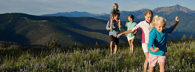 A young couple with three young children walk in a mountain meadow. Mountains in the background.