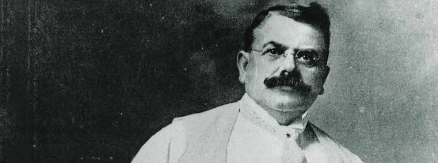 Black and white photo of Wallace C. Abbott.  He has short dark hair and a full, dark mustache and is wearing glasses and a white shirt, a suit vest and a tie.